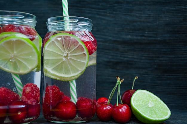 爽やかな夏の飲み物とフルーツ。チェリー、ラズベリー、ライムから作られた飲み物。暗い背景の木。