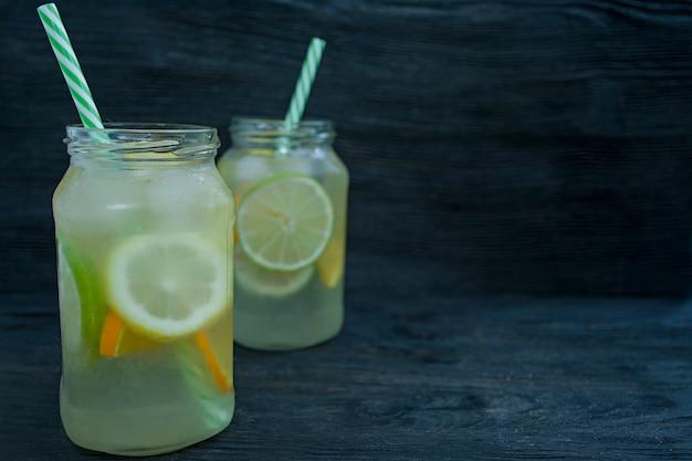 柑橘系の果物からさわやかな夏の飲み物。ライム、レモン、オレンジから飲む。暗い背景の木。