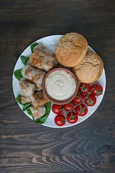 ソースと白い皿に肉と野菜の春巻きを添えて。コンクリートの下の明るい背景。