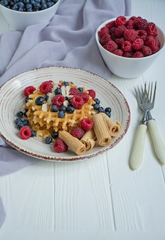 朝食に新鮮なフルーツのワッフル。日当たりの良いワッフル。白い木製の背景。