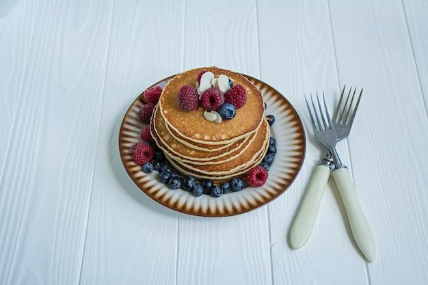 青い木製の背景に新鮮なベリーと古典的なアメリカのパンケーキ。フルーツのパンケーキ。夏の自家製朝食。