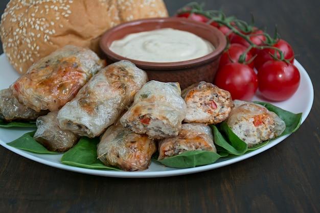 ソースと白い皿に肉と野菜の春巻きを添えて。