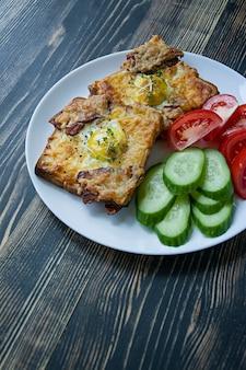 卵、野菜、ベーコン、暗い背景の木のグリルサンドイッチ