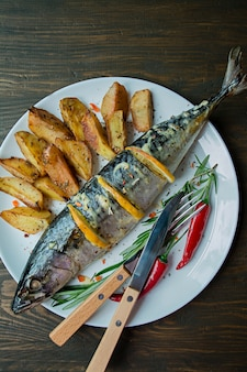 スパイス、ハーブ、野菜で飾られた皿に揚げたサバ