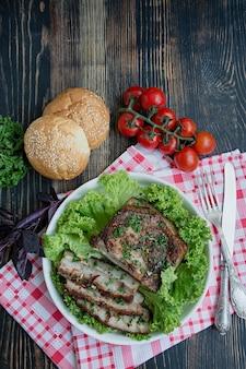焼き豚バラ肉のスパイス。スライスした胸肉、グリーン添え。ウクライナの伝統的な料理。
