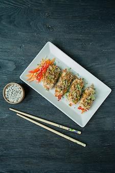 暗いまな板の上に野菜と新鮮な鶏の胸肉ロール