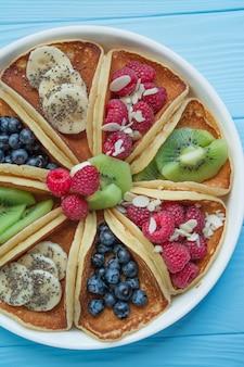 青い木製の新鮮なベリーのパンケーキ。フルーツのパンケーキ。夏の自家製朝食。