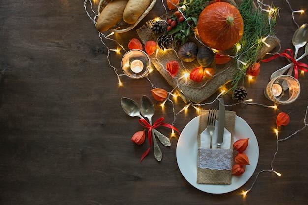 感謝祭のディナー。ハロウィーンディナー。カボチャ、紅葉、秋の季節の装飾が施されたお祝いテーブル。