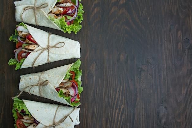 Мексиканское блюдо. завернутый буррито с курицей и овощами крупным планом