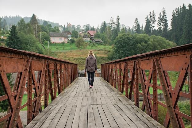 山の橋。山の橋の上を歩く少女。
