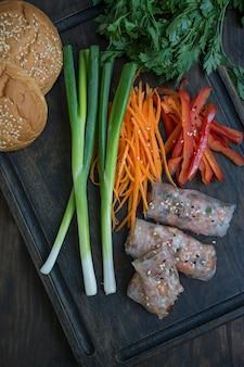 まな板の上で提供される肉と野菜の春巻き。