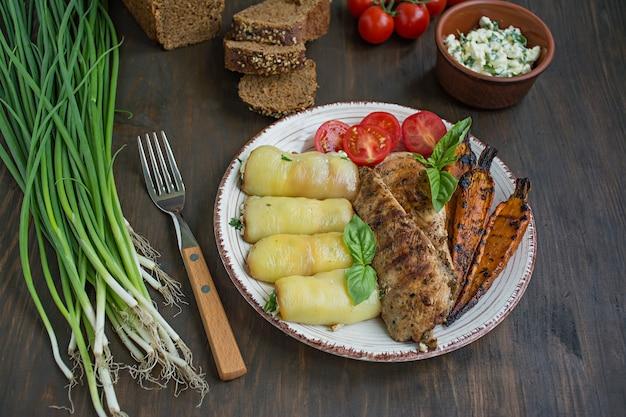 グリルしたチキンの切り身、焼き野菜、ピーマンロール。木製。
