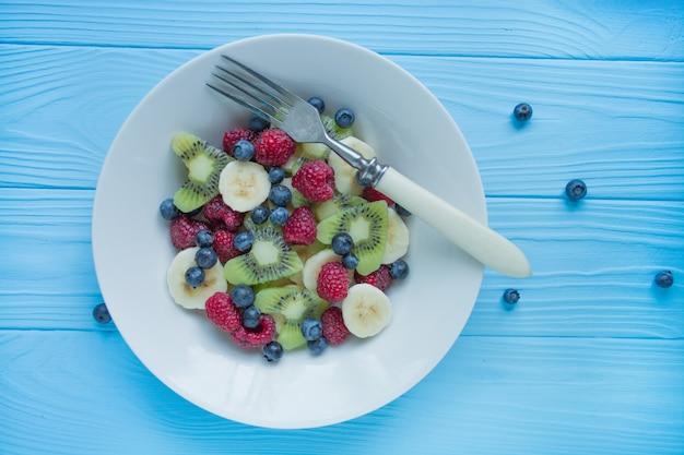 フルーツプレート。キウイ、バナナ、ブルーベリー、ラズベリーのフルーツサラダ。木材 。