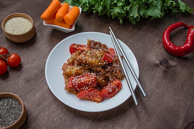 ゴマとハーブの温かい韓国風ナスとトマトのサラダ。アジア料理。ベジタリアン料理。木材 。