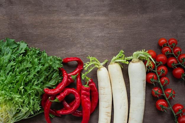 木製の背景に新鮮な野菜のセット。唐辛子、大根、チェリー、テーブルの上のサラダ