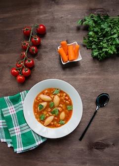 パスタとハーブ入りミネストローネスープ。イタリア料理。暗い背景の木