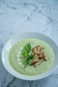 ズッキーニのクリームスープは白い皿で提供しています。