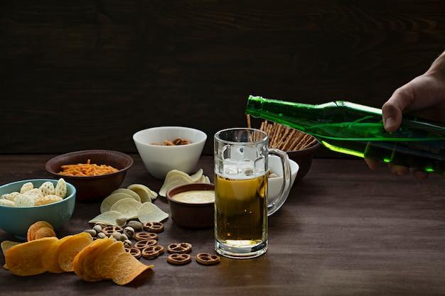 男性の手はビールを注ぐ。プレッツェルと様々なスナックとビール。