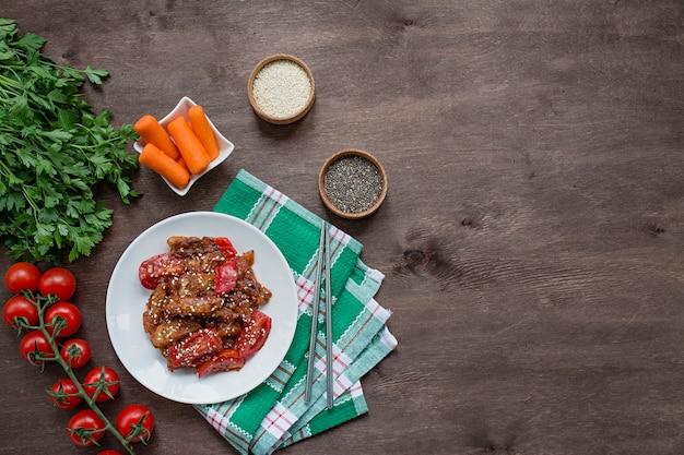 ごまとハーブのアジア料理を添えた韓国風の温かいナスとトマトのサラダ。ベジタリアン料理。木材 。 。