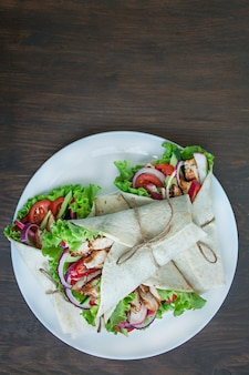 Мексиканское блюдо. тако с курицей и овощами крупным планом на деревянной поверхности.