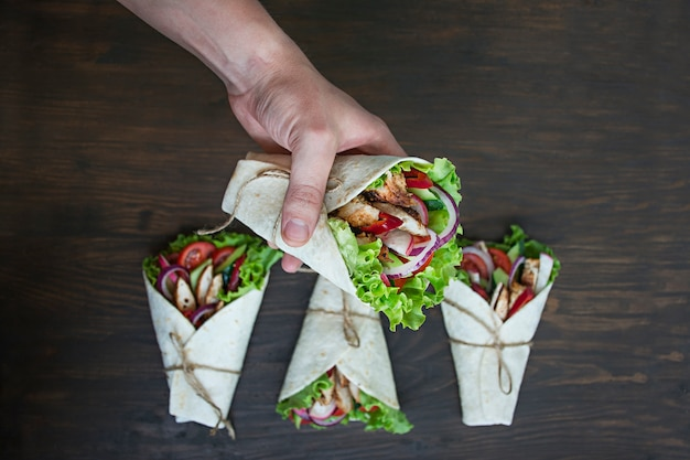 メキシコ料理。木製の表面に鶏肉と野菜のクローズアップとタコス。