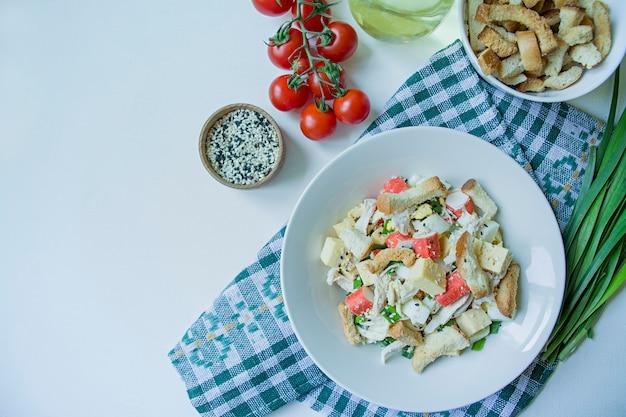 Салат с крекерами, крабовыми палочками, куриным филе, свежей зеленью и твердым сыром