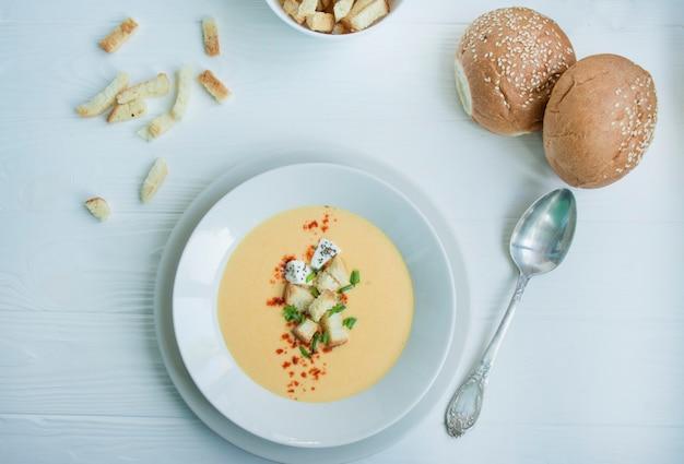 Сырный суп с крекерами, зеленью и сыром фета. крем-суп подается в белой тарелке. белый