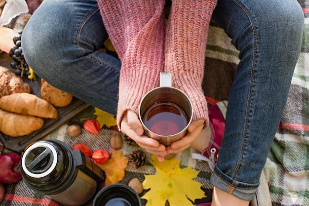 公園で秋のピクニック、暖かい秋の日。女の子は手にお茶の入ったカップを持っています。黄色の紅葉の毛布の上に花のバスケット。秋のコンセプト。