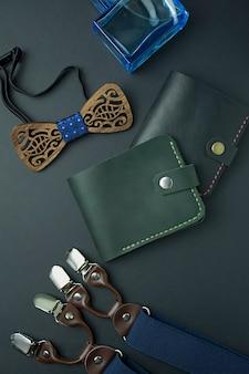メンズアクセサリー。暗い背景にメンズ財布、メンズバタフライ、サスペンダー、香水。