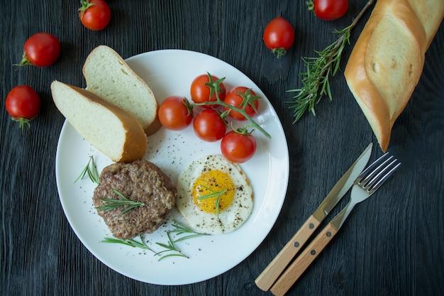 スパイスで目玉焼きとビーフステーキを白い皿に提供しています。アメリカ料理