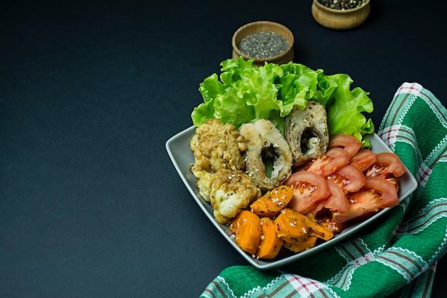 焼き魚と野菜。フィッシュプレート。適切な栄養。エコフード。暗い背景。テキスト用のスペース。