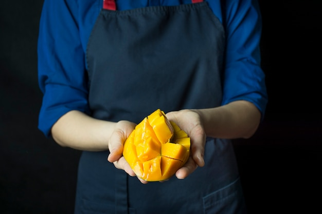 料理人の手で新鮮なマンゴー。エキゾチックなフルーツ。熟したマンゴー。バランスの取れた食事。