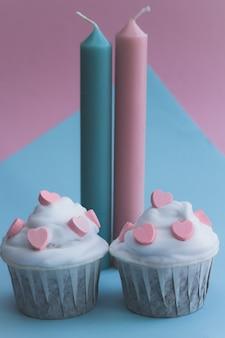 Симпатичные кексы, украшенные розовыми сердечками на розовом и голубом