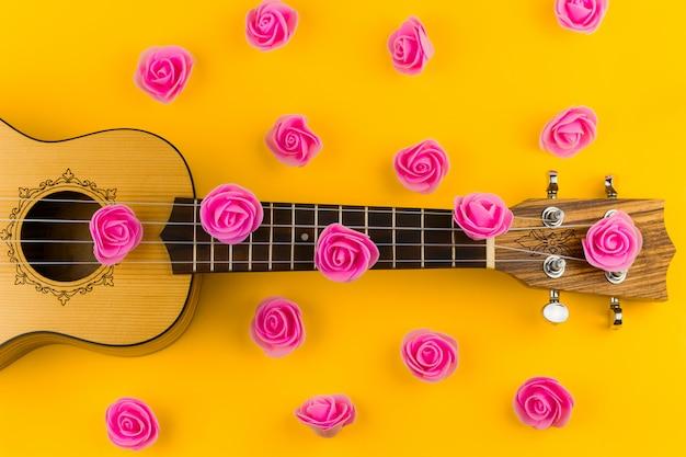 Взгляд сверху картины гитары и цветков розы на ярком желтом цвете