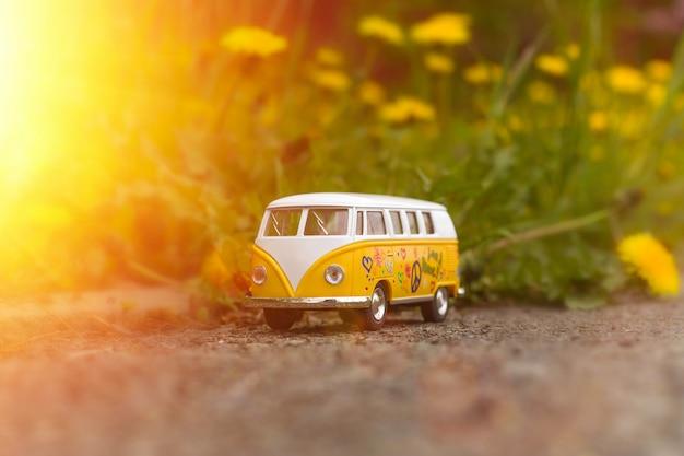 日光の下で咲くタンポポのレトロなバスのおもちゃ