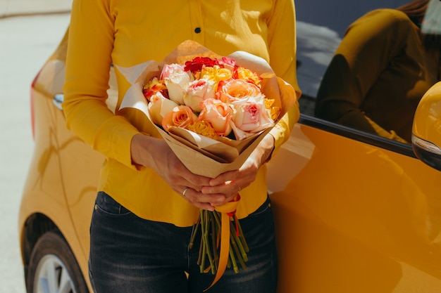 Женщина в желтой блузке с букетом желтых роз возле желтого автомобиля