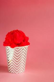 Красное фруктовое мороженое или замороженный йогурт в полосатой чашке на розовом