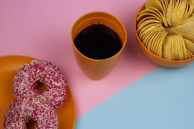 トップビューコーラガラス、チップボウル、ドーナツプレート、ピンクとブルーの背景。不健康な食品のコンセプト