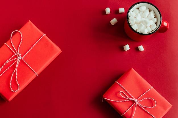 Вид сверху красные подарочные коробки и чашка с рамкой зефир на красном фоне