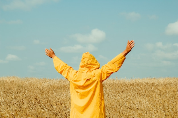 Счастливый молодой человек, носить желтый плащ, стоя в пшеничном поле