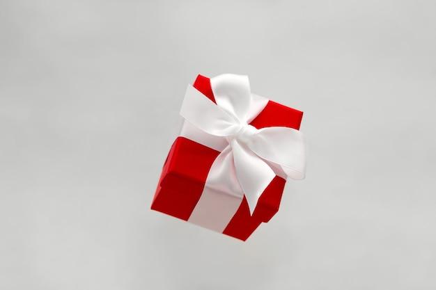 Праздничная красная подарочная коробка с левитирующим белым бантом, изолированная на сером фоне