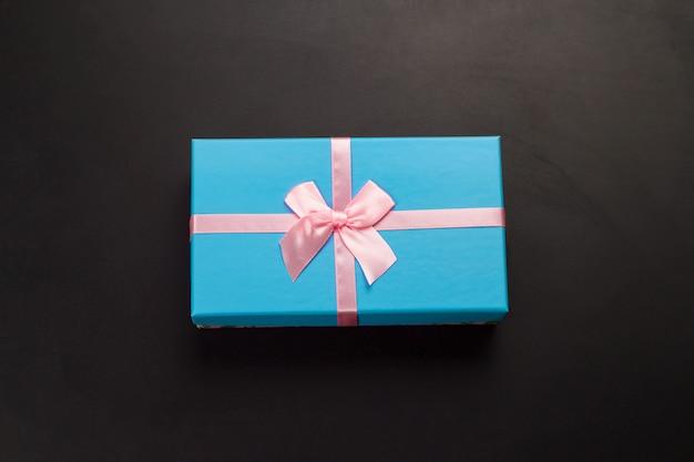 Вид сверху синей подарочной коробке на черном фоне