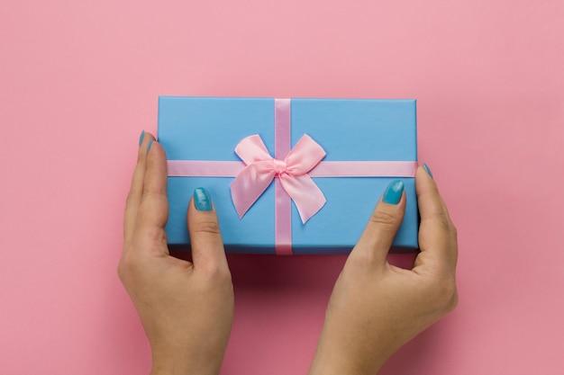 柔らかいピンクの背景にお祝いのピンクの弓と青いギフトボックスを保持しているトップビュー女性手