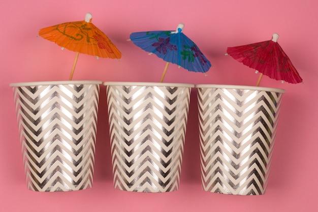 Вид сверху три бумажных стаканчика с коктейльным зонтиком розового фона