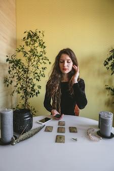 ルーン文字のカードで黒いコーデュロイドレスの美しい若い女性を推測しています