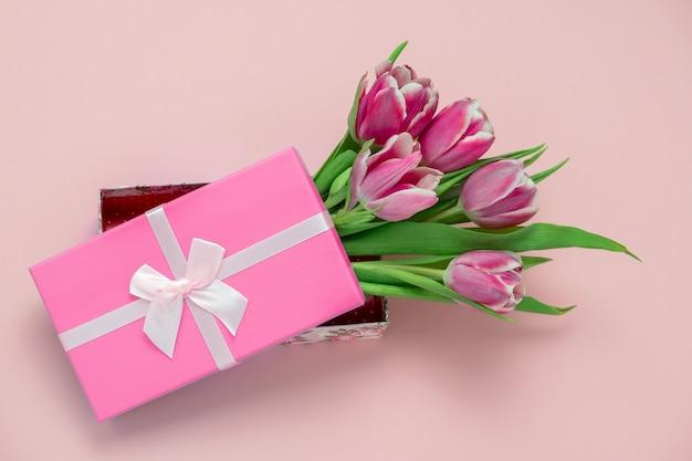 Вид сверху розовых тюльпанов в коробке с розовой атласной лентой, бантом на пастельно-розовом