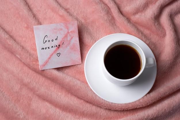 Вид сверху кофейная чашка на розовом одеяле
