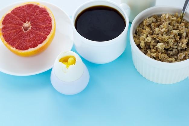 健康的な朝食牛乳瓶、コーヒー、オートミール、ゆで卵、グレープフルーツ