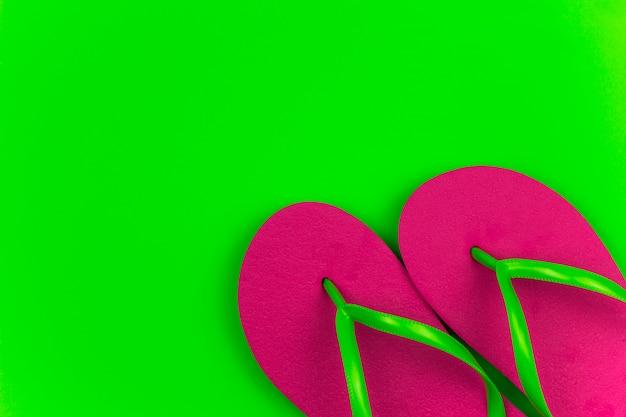 夏の明るいピンクのフリップフロップグリーンの背景
