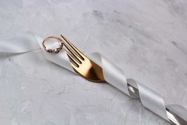 Вилка украшена белой атласной лентой для свадьбы с золотым кольцом